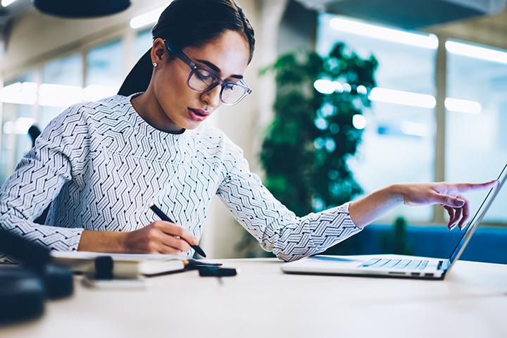Mujer escribiendo y tomando desiciones con una laptop