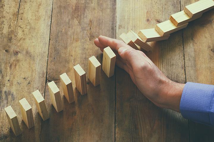 Mano detiene bloques de madera antes de caer